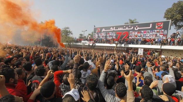 Egyptian soccer fans of Al-Ahly football club celebrate in front of their club premises in Cairo on Saturday. An Egyptian court sentenced 21 people to death in relation to a soccer stadium riot last February.