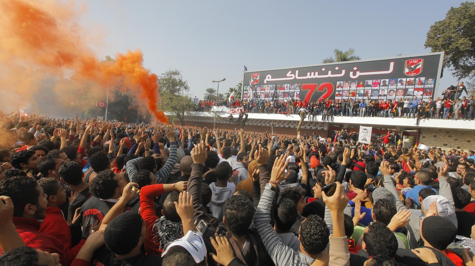 Egyptian soccer fans of Al-Ahly football club celebrate in front of their club premises in Cairo on Saturday. An Egyptian court sentenced 21 people to death in relation to a soccer stadium riot last February. (AP)