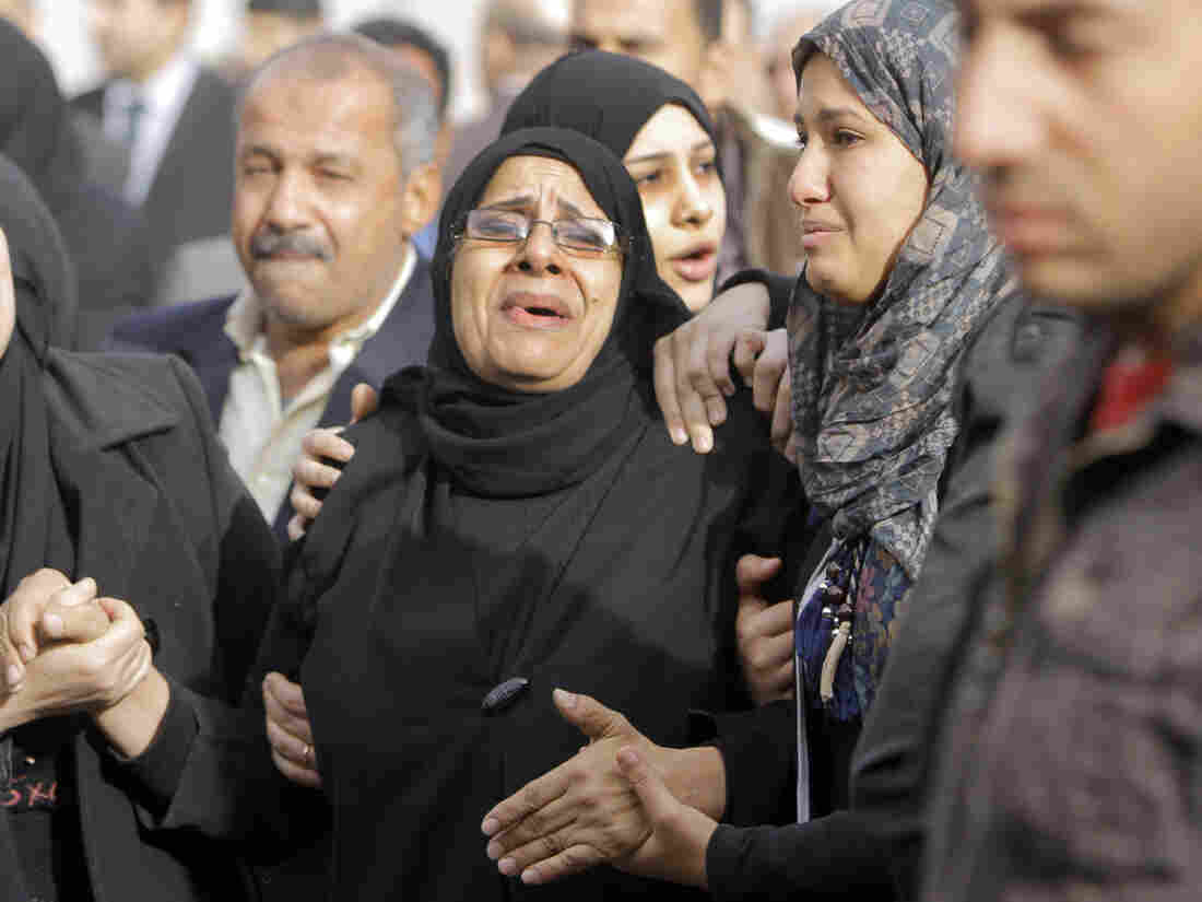 Relatives of the Egyptian policemen who were killed in Port Said grieve during their military funeral in Cairo on