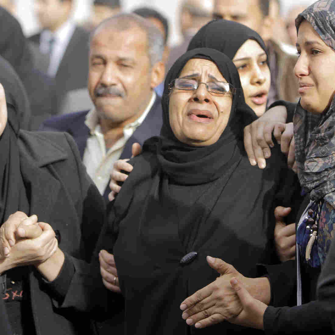 Relatives of the Egyptian policemen who were killed in Port Said grieve during their military funeral in Cairo on Sunday.