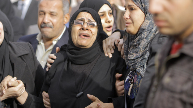 Relatives of the Egyptian policemen who were killed in Port Said grieve during their military funeral in Cairo on Sunday. (AP)