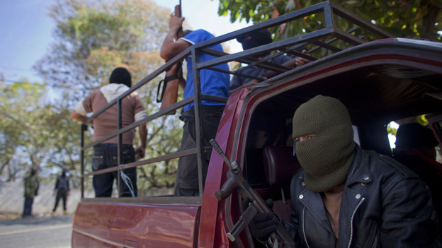 Masked and armed men guard a roadblock near the town of Ayutla, Mexico, on Jan. 18. Hundreds of men in the southern Mexican state of Guerrero have taken up arms to defend their villages against drug gangs. (AP)