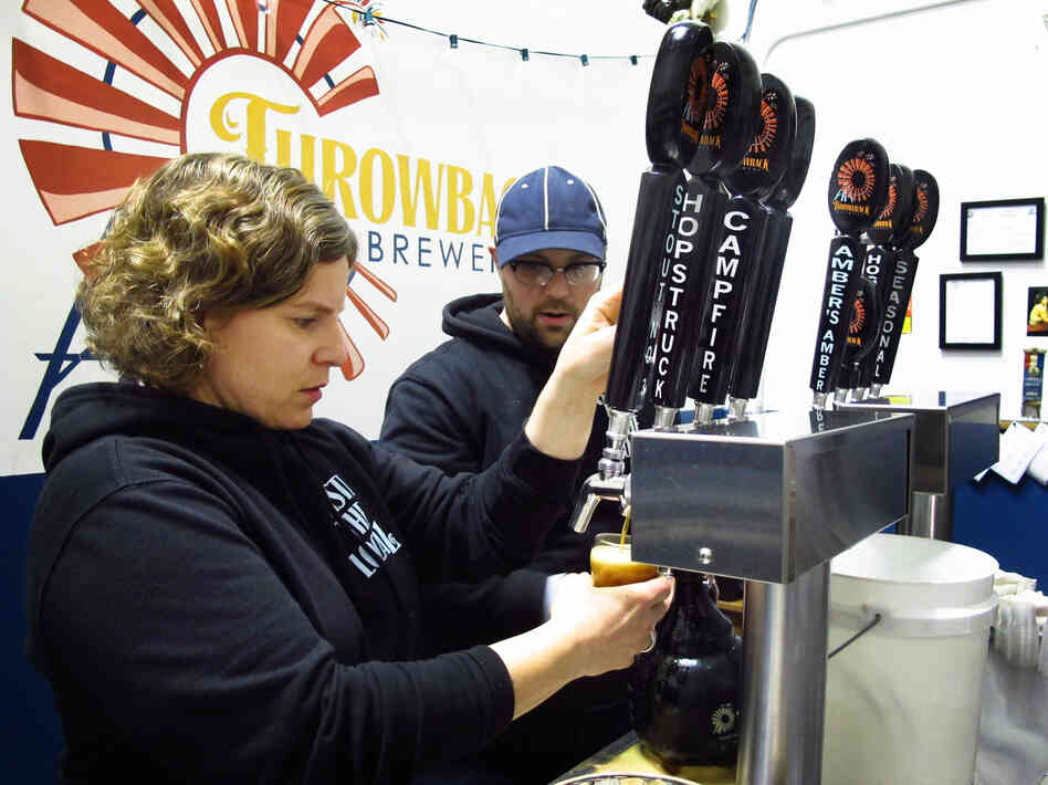 Throwback Brewery co-owner Nicole Carrier and assistant brewer Chris Naro pour beer for customers at their North Hampton, N.H., t