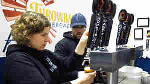 Throwback Brewery co-owner Nicole Carrier and assistant brewer Chris Naro pour beer for customers at their North Hampton, N.H., taproom.