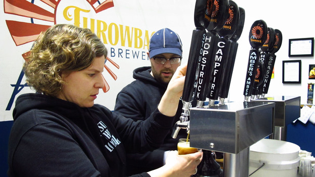 Throwback Brewery co-owner Nicole Carrier and assistant brewer Chris Naro pour beer for customers at their North Hampton, N.H., taproom. (NHPR)
