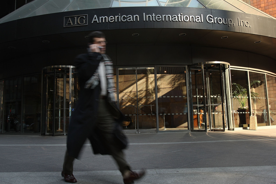 A man walks by an American International Group (AIG) building in 2009.