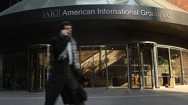 A man walks by an American International Group (AIG) building in 2009. (Getty Images)