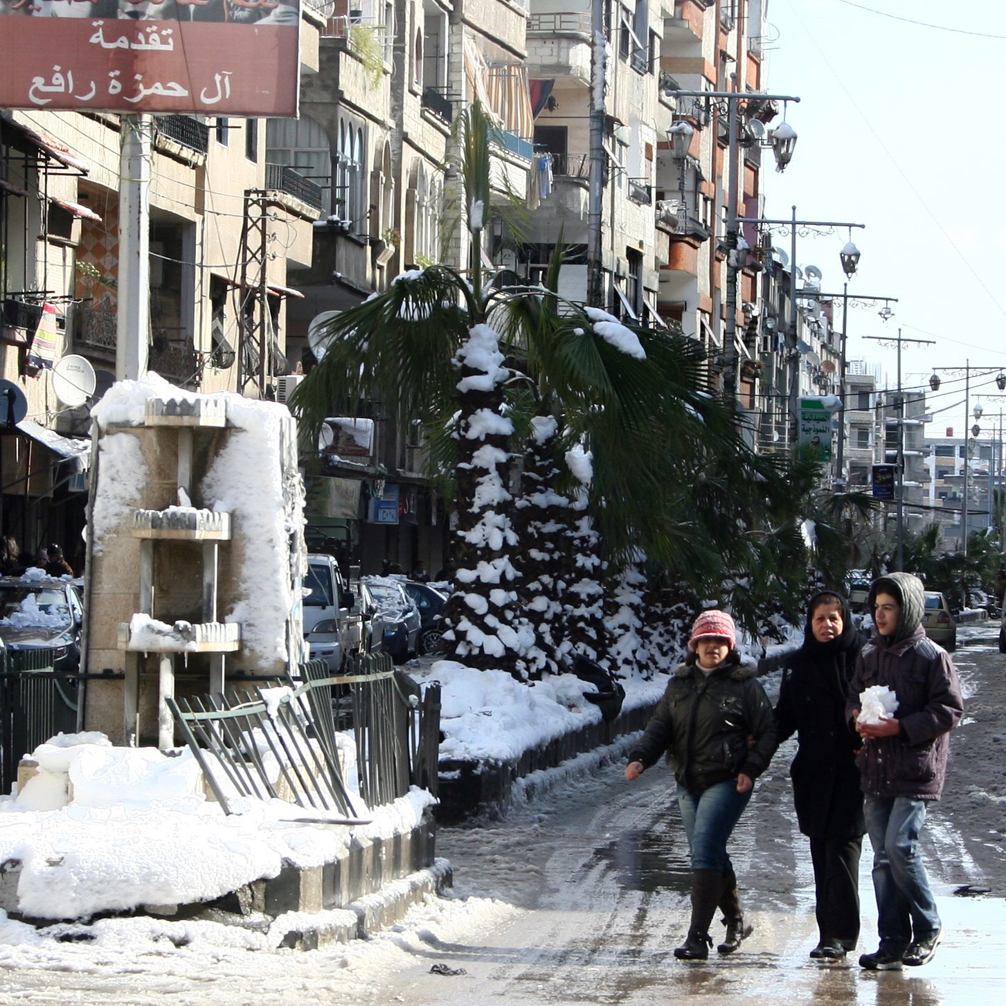 Damascus residents still get out during the day, but the streets empty at night. Here, Damascenes walk past a poster of President Bashar Assad on Jan. 10, following a heavy snow.