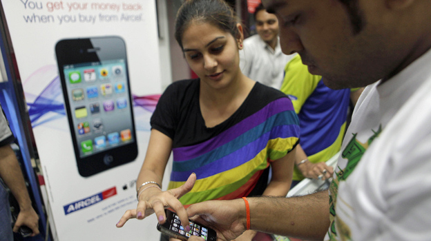 A salesperson demonstrates the Apple iPhone 4 in New Delhi, India. While mobile device use is growing rapidly in emerging markets, Apple's current product line may prove prohibitively expensive for many consumers. (AP)