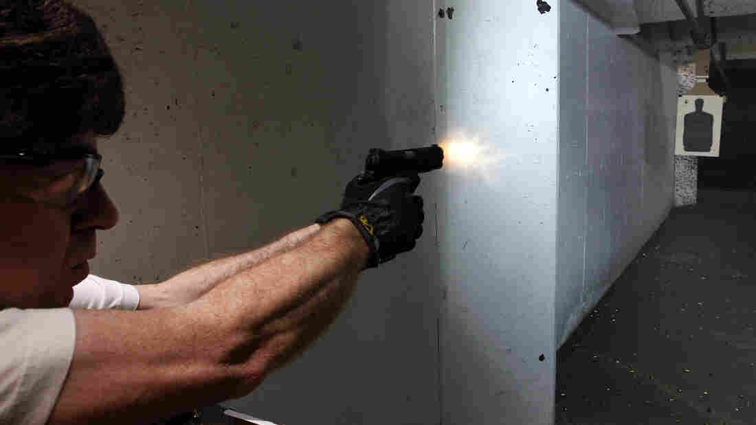 """The NRA and some concealed-carry activists say the best defense against gun violence is armed """"good guys."""" Here, a man fires his pistol at an indoor range in Aurora, Colo., last summer."""