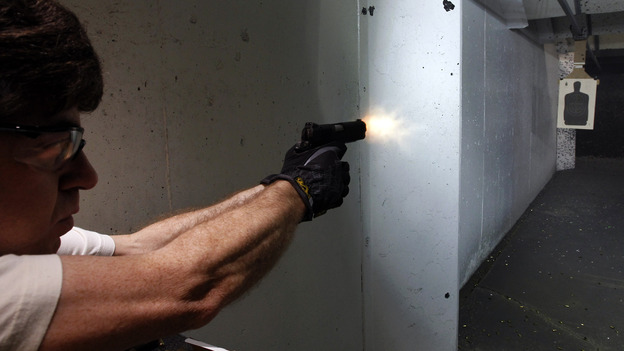 "The NRA and some concealed-carry activists say the best defense against gun violence is armed ""good guys."" Here, a man fires his pistol at an indoor range in Aurora, Colo., last summer. (AP)"