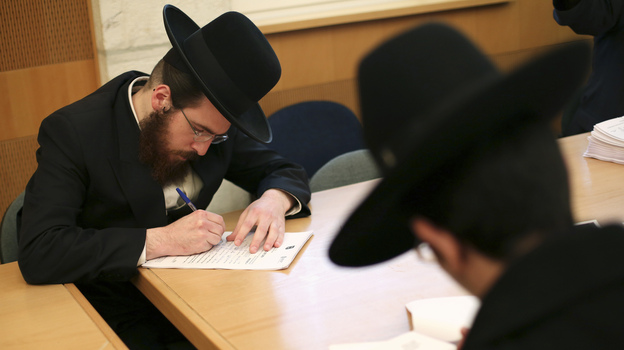 Ultra-Orthodox Jews are not required to perform military service in Israel, and the issue is subject to intense debate following the country's election last week. Here, ultra-Orthodox men sign up for alternate civilian service earlier this month. (Reuters /Landov)