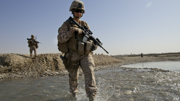 U.S. troops in Afghanistan appear to have mixed feelings about the decision lifting the ban on women in combat positions. Some women already operate in combat zones. Hospital Corpsman Shannon Crowley is shown here with her Marine Corps team in Musa Qala, Afghanistan, in November 2010. (Getty Images)