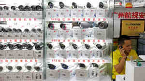A man sells surveillance cameras at the main electronics market in Tienhe district, Guangzhou, in southern China's Guangdong province, on Aug. 8.