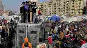 Protesters surround a burned Egyptian army vehicle in Cairo on Jan. 29, 2013.