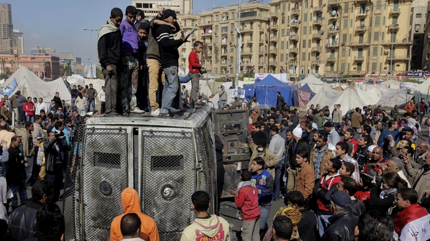 Protesters surround a burned Egyptian army vehicle in Cairo on Jan. 29, 2013. (AP)