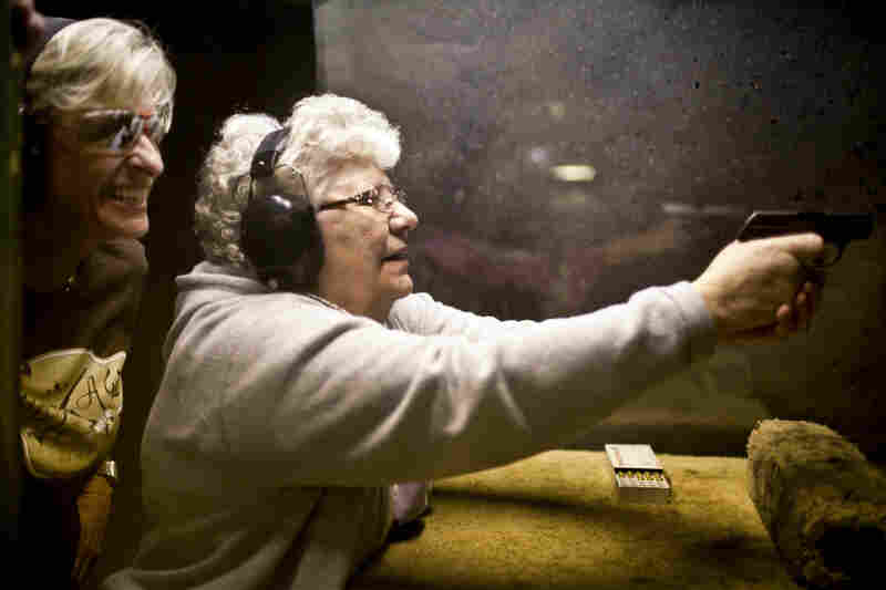 "Renee Blaine (left), a member of the women's shooting league A Girl and A Gun, gives Delores Mouton, 75, tips on how to fire a gun during a ""girls' night out"" event at the Eagle Peak Shooting Range in Leander, Texas. Mouton had never shot a gun before this evening, but hit a bull's-eye her first time. She says she is learning to shoot for personal protection."
