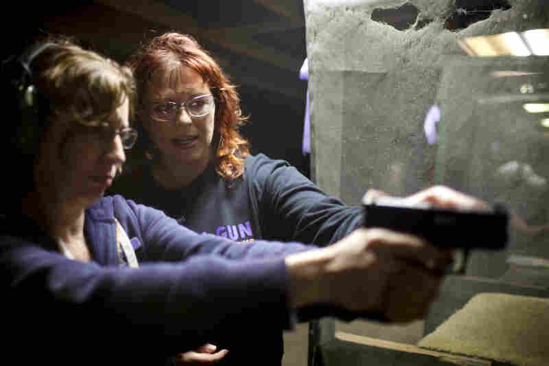 """Crowder (right) helps Maria Acosta, a new league member, fire her weapon. Acosta, who has a concealed-weapons permit, joined the league to feel more confident in her shooting in order to protect her home. She says being around the other women makes her feel sure of herself, and not """"silly."""""""