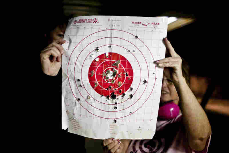 """Kosarek checks her target with Crowder. According to Crowder, some women's shooting groups hire certified babysitters, and others have volunteers who take turns watching the kids, """"kind of like day care at church."""""""