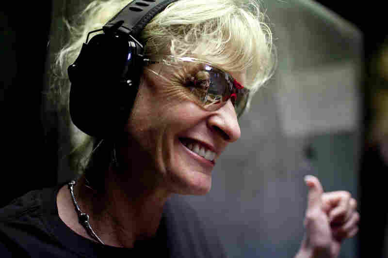 Blaine smiles while giving pointers on technique to Courtney Bird (reflected in glasses). The women in the group go out to dinner after their time at the range to socialize.