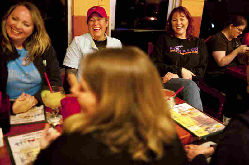 Shooting range instructor Julianna Crowder (second from right) has dinner with fellow members of the shooting league A Girl and A Gun, in Leander, Texas.