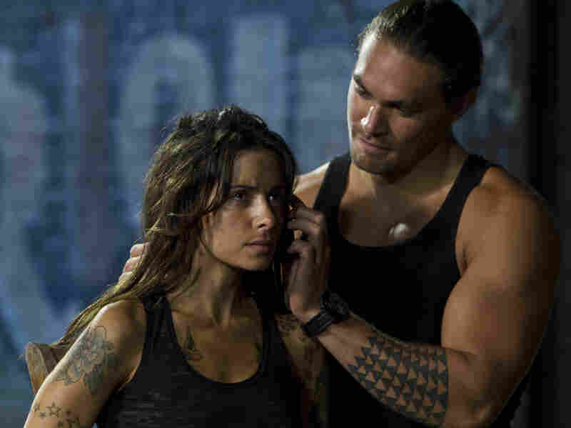 Sarah Shahi's tattoo artist — who has ties to both Kang and Stallone's characters — falls into the clutches of a mob enforcer (Jason Momoa).