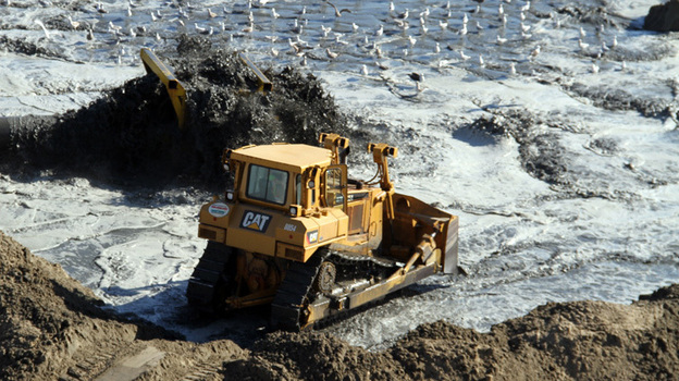 Ongoing beach nourishment, like this project in Viriginia Beach, has been the topic of debate. Some people say it's needed to protect beach communities; others decry the costs. (U.S. Army)