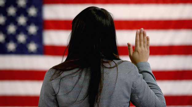 A woman takes the oath of allegiance during a naturalization ceremony at the district office of the U.S. Citizenship and Immigration Services in Newark, N.J. (Getty Images)