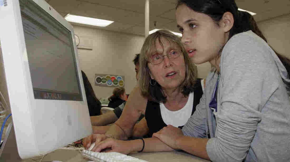 Palo Alto High School teacher Esther Wojcicki helps student Allison Wyndham at a computer during class.