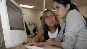 Palo Alto High School teacher Esther Wojcicki helps student Allison Wyndham at a computer during class.