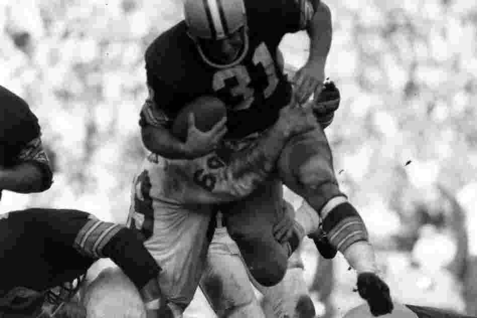Green Bay Packer Jim Taylor is tackled by the Chiefs' Sherrill Headrick.