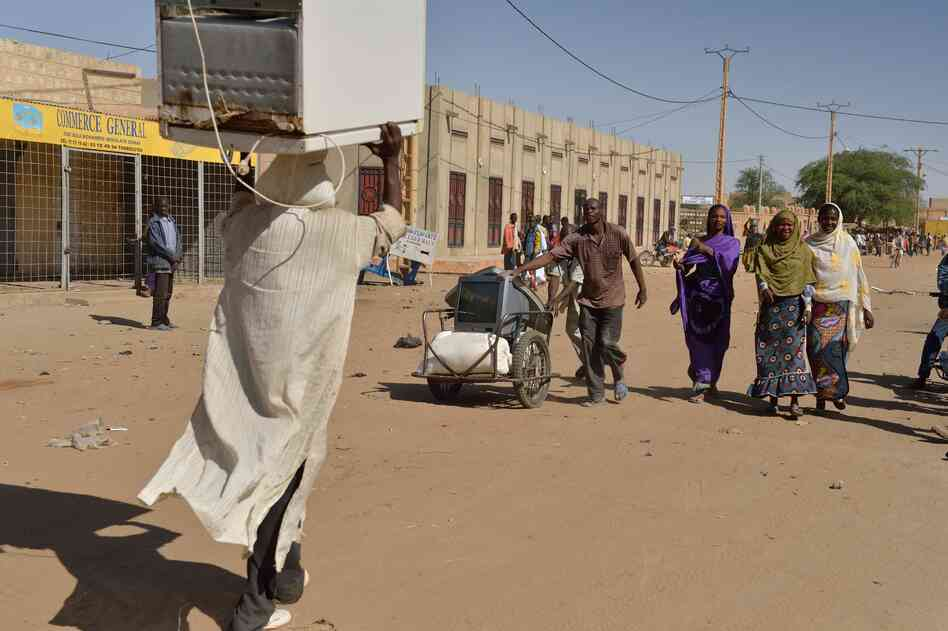 Looters in Timbuktu leave with a TV and a fridge Tuesday, after French-led troops free