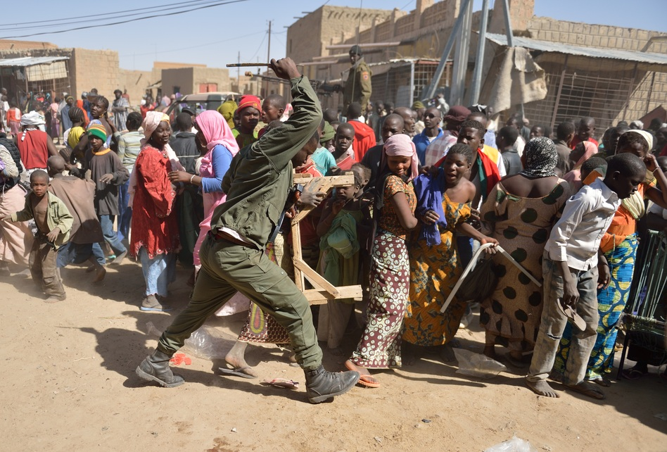 A Malian soldier tries to disperse looters in the streets of Timbuktu on Tuesday. (AFP/Getty Images)