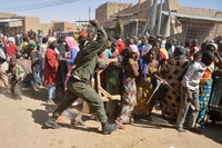 A Malian soldier tries to disperse looters in the streets of Timbuktu on Tuesday.