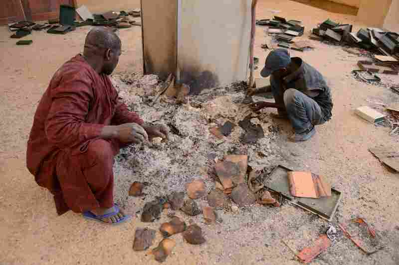Men look over ancient manuscripts Tuesday that were destroyed at the Ahmed Baba Institute in Timbuktu. The manuscripts date back to the 13th century.