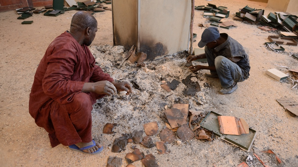 Men recover burnt ancient manuscripts at the Ahmed Baba Institute in Timbuktu on Tuesday. (AFP/Getty Images)