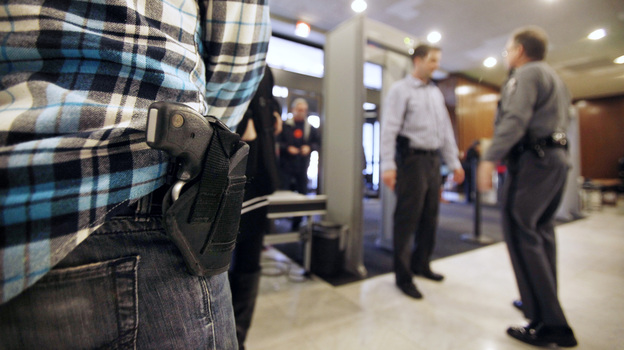 "A concealed handgun permit holder waits to enter the General Assembly building in Richmond, Va., on Jan. 21. Known as ""gun lobby day,"" crowds of gun owners visited the capital to argue in favor of gun rights. Most states in the U.S. allow people to openly carry guns in certain public places. (Courtesy of Richmond Times-Dispatch)"