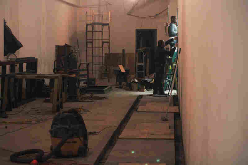 Workers on the main floor close off a former eyeglass store as they prepare to install electrical switching equipment.