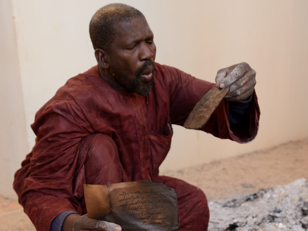 A man attempts to salvage burnt manuscripts at the Ahmed Baba Institute in Timbuktu, Mali, on Tuesday. While some of the ancient manuscripts were destroyed by Islamist radicals, reports indicate that most were hidden and therefore survived. (AFP/Getty Images)