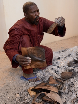 A man attempts to salvage burnt manuscripts at the Ahmed Baba Institute in Timbuktu, Mali, on Tuesday. While some of the ancient manuscripts were destroyed by Islamist radicals, reports indicate that most were hidden and therefore survived.