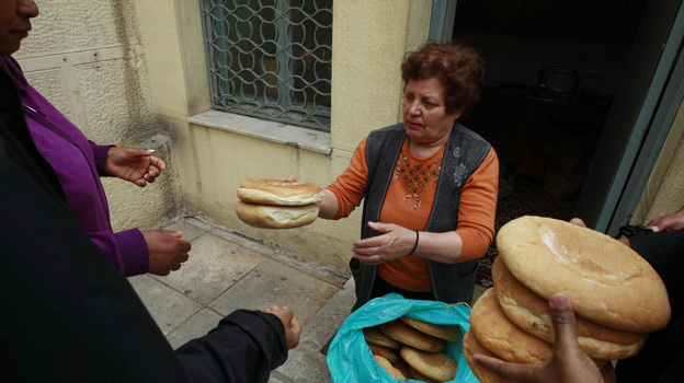 Georgia Kolia, 63, has two adult children, both unemployed. She works as a volunteer distributing loaves of bread at the Agia Zonis Orthodox church soup kitchen for the poor in Athens, Greece, in April 2012. (Reuters/Landov)