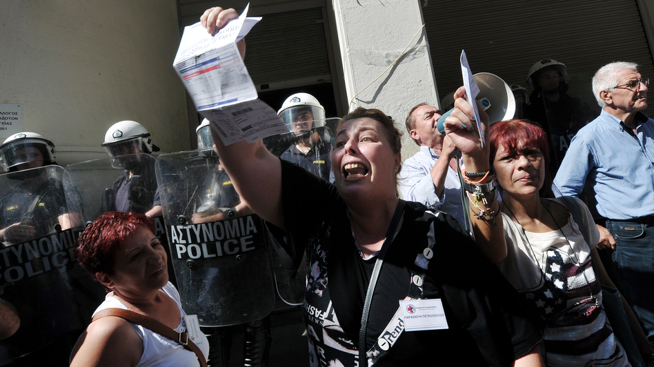 Unpaid for five months, nurse Paraskevi Petropoulou holds her unpaid electricity bill outside the Ministry of Health in Athens during an anti-government protest on Sept. 28, 2012. (AFP/Getty Images)