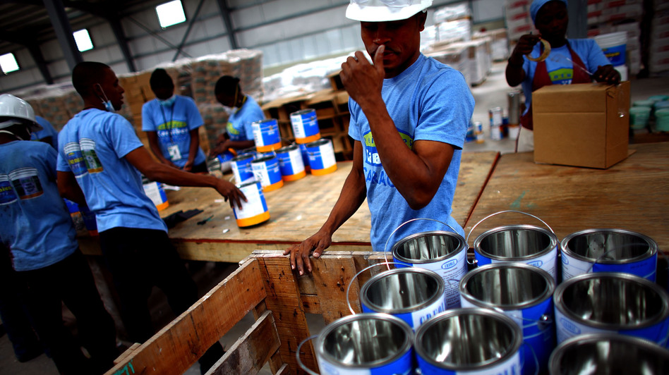 Workers arrange paint buckets before they are filled at a warehouse in the Caracol Industrial Park, which Haiti is billing as the largest in the Caribbean. (NPR)