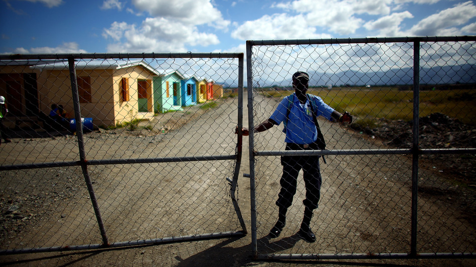 An armed guard keeps watch over a new, USAID-funded housing complex. The homes will be offered to people who work at Caracol. (NPR)