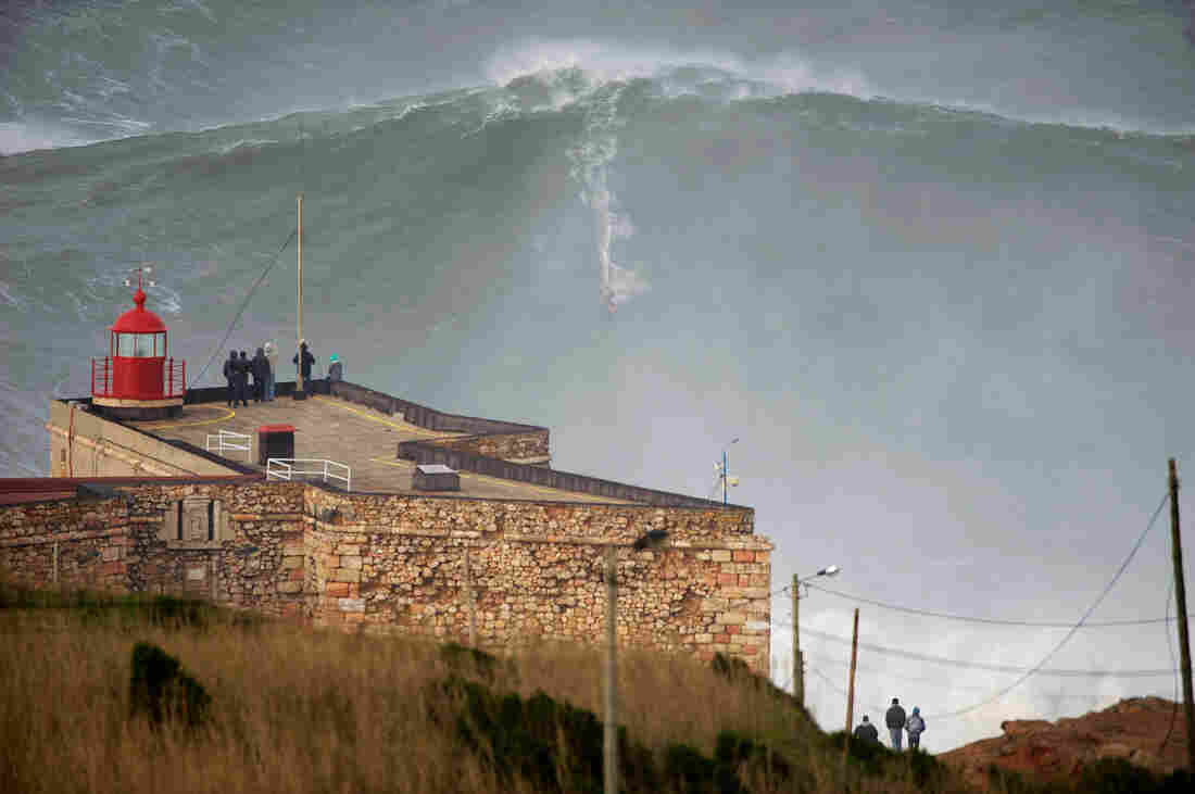 """American surfer Garrett """"GMAC"""" McNamara rides what could be, if confirmed, the biggest wave conquered in history as a crowd watches Monday in Nazare, Portugal."""
