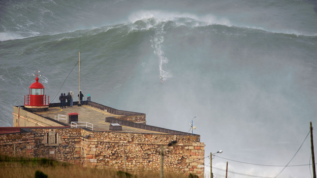 """American surfer Garrett """"GMAC"""" McNamara rides what could be, if confirmed, the biggest wave conquered in history as a crowd watches Monday in Nazare, Portugal. (Barcroft Media /Landov)"""