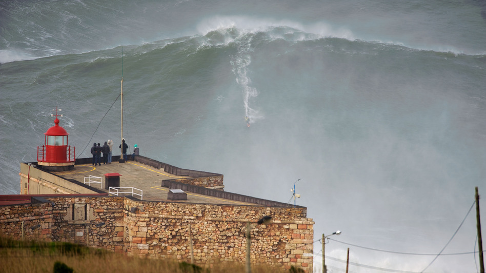 "American surfer Garrett ""GMAC"" McNamara rides what could be, if confirmed, the biggest wave conquered in history as a crowd watches Monday in Nazare, Portugal. (Barcroft Media /Landov)"