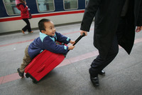 A boy hitches a ride on a suitcase as he waits to board a train at Beijing West Railway Station during the peak of travel for the Chunyun Spring Festival, in February 2007.