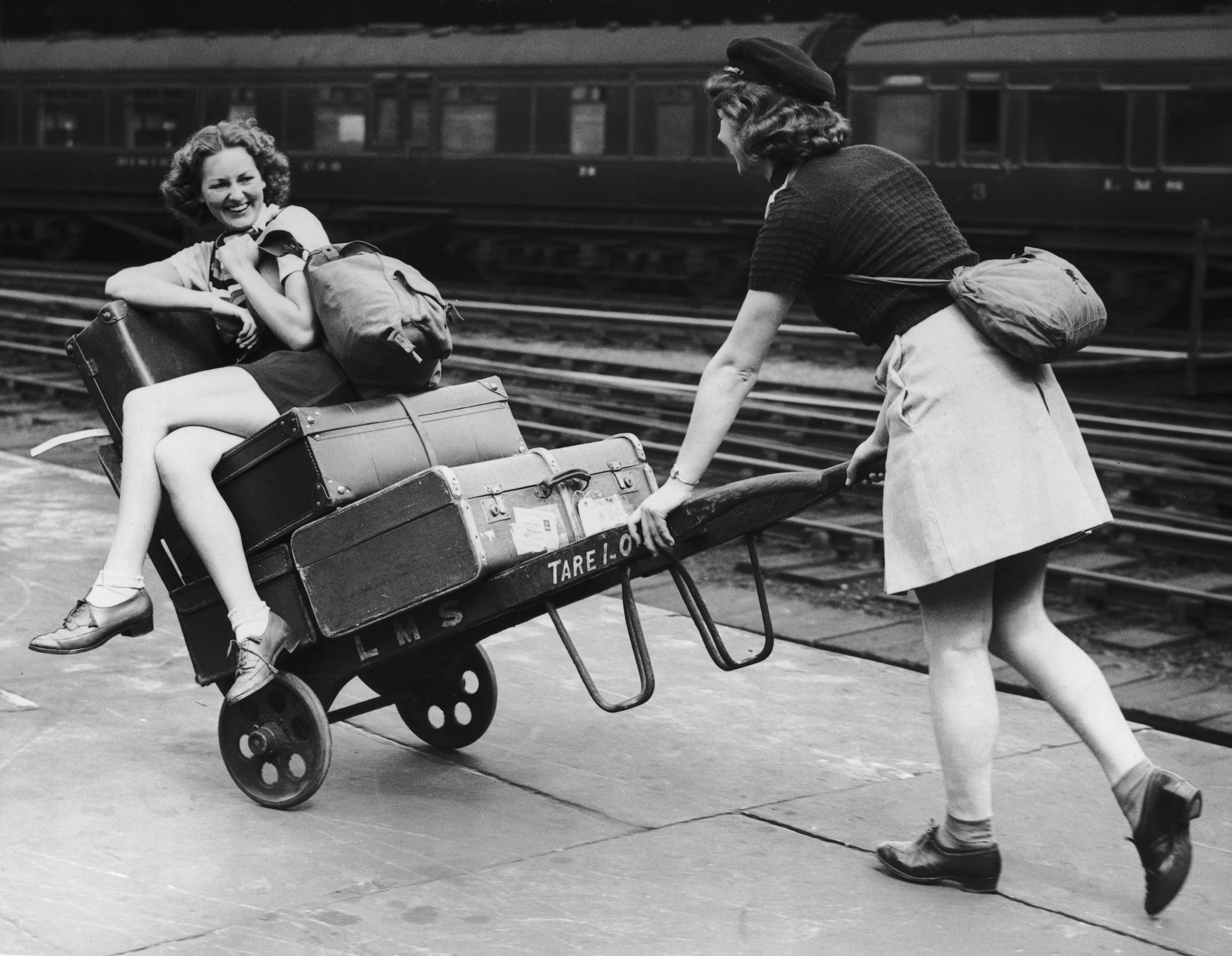 Two holidaymakers amuse themselves with a porter's trolley as they wait for their train at Euston Station in London in August 1939.