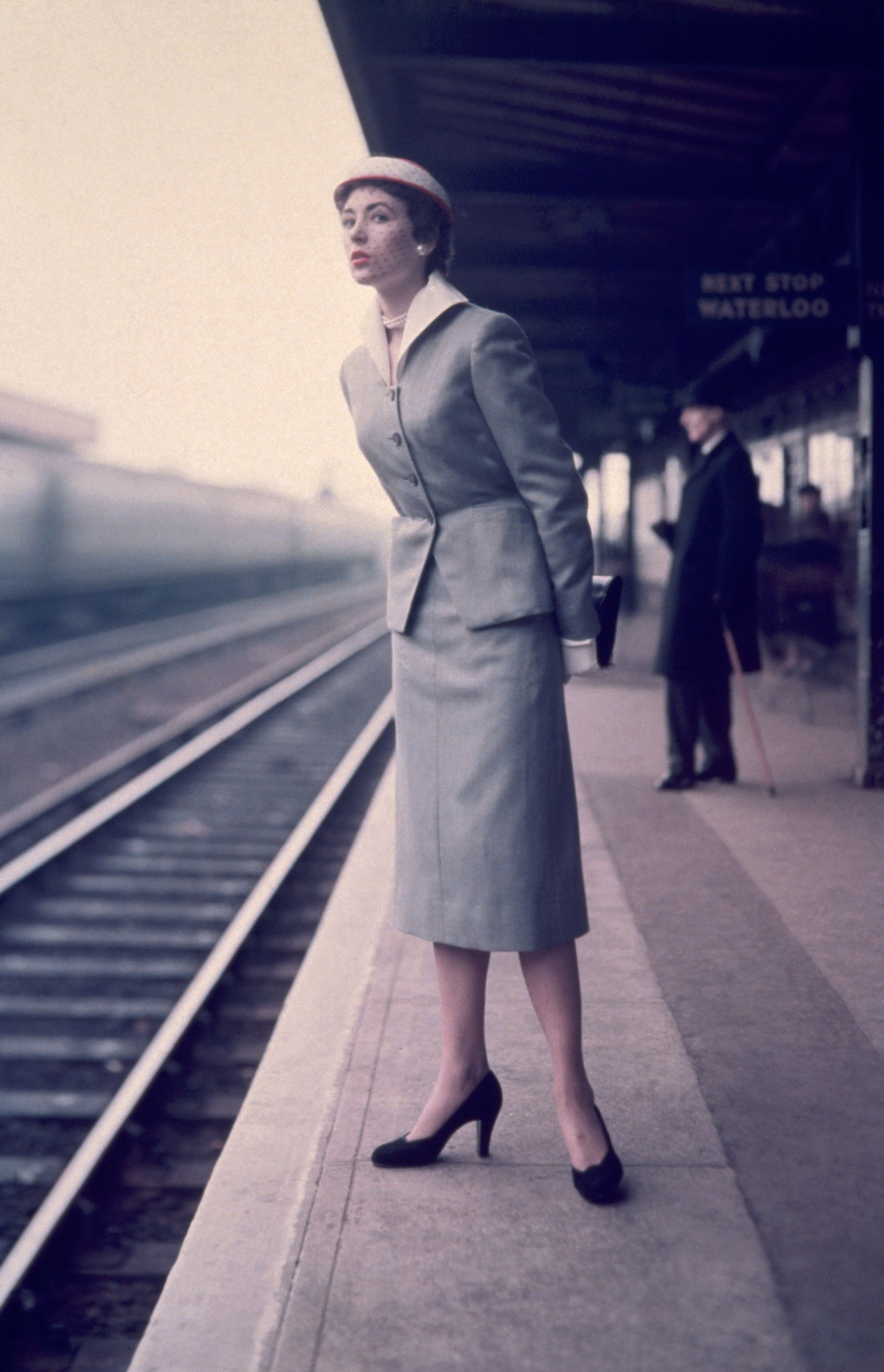 A woman stands on a station platform, watching for her train.